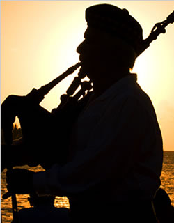 image bagpiper piping at sunset